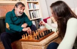 young woman and elderly man playing chess