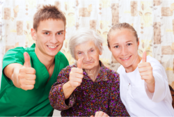 caregivers and elderly woman showing thumbs up